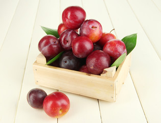 Ripe plums in wooden box on wooden table close-up
