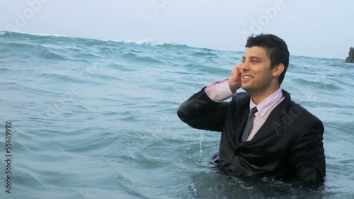 Business man calling cell phone in the sea HD