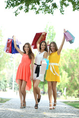 Three beautiful young woman with shopping bags in park