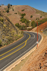 Road curves by steep hill of different colors