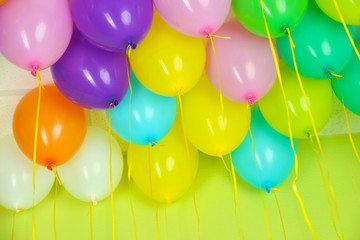 Colorful balloons on green wall background