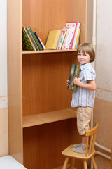Preschooler stands on chair with book