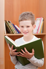 Smiling boy holds big green book