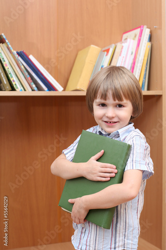 Boy holds book against bookcase