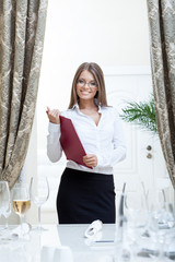Image of friendly hostess posing in restaurant