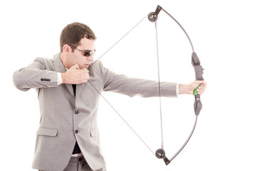 Determined handsome businessman aiming at target with bow