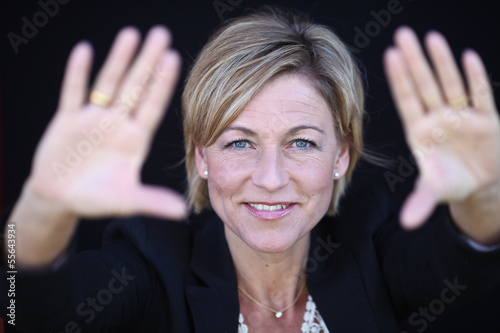 Woman standing with her two hands open to frame her head. Shot i