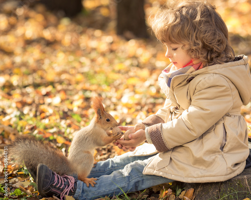 Child feeds a little squirrel