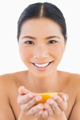 Smiling pretty woman holding orange