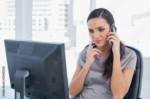 Thoughtful attractive businesswoman having a phone conversation