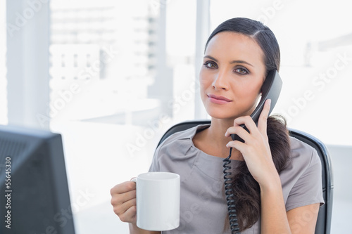 Serious secretary answering phone and drinking coffee