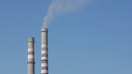 Industrial smokestacks against the blue sky