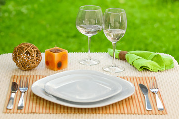 Empty plate with fork and knife against meadow. Table