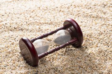 砂の背景に砂時計のアップ