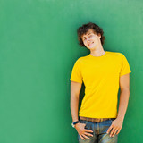 man with curly hair in a yellow T-shirt