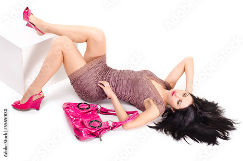 Girl lying on the floor and keeps on hand bag