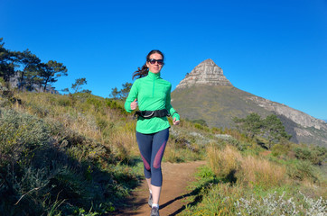Woman runner runs trail near Table mountain, Cape Town