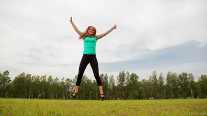 Young woman tumbling wheel, acrobatics on a green glade