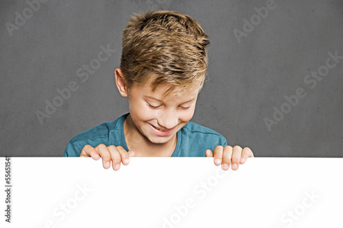 Child looking over white Wall