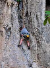 man climbing on the rock route summer