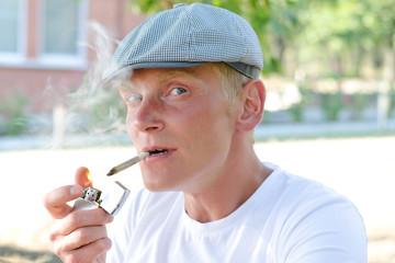 Happy smoker lighting up a cigarette