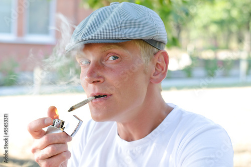 Happy smoker lighting up a cigarette