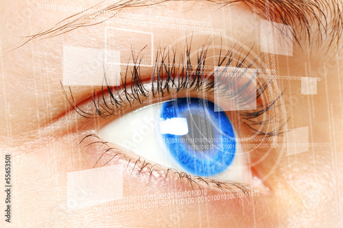 Woman blue eye looking on digital virtual screen close-up.