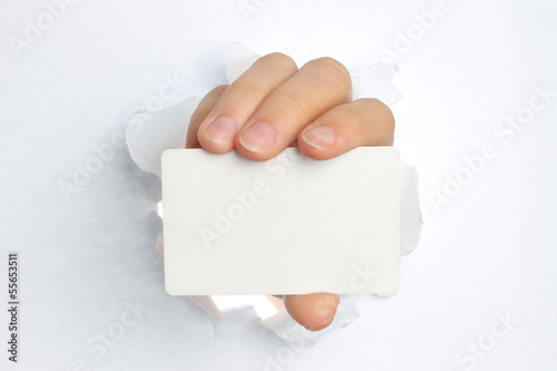 Hand holds white card through white torn paper .