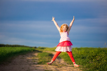 Happy little girl jumping in front of blue sky