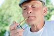 Mature man lighting up a cigarette