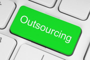 Green outsourcing button on white keyboard.