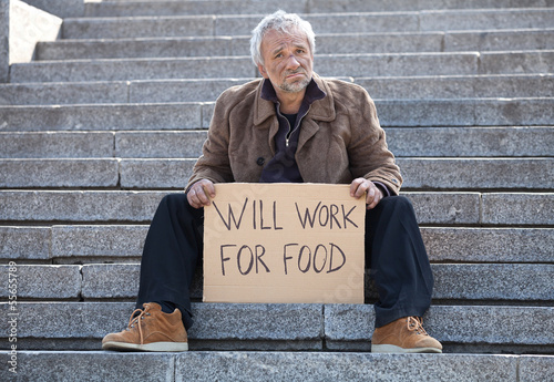Will work for food. Depressed senior man sitting on stairs and h