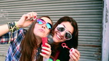 Hipster girls smiling and laughing while blowing bubbles