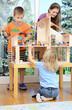 Babysitter und Kinder spielen mit Puppenhaus