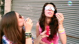 Two teenage girls having fun blowing bubbles