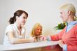 Frau gibt Chipkarte an Arzthelferin