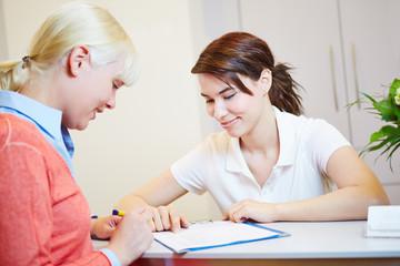 Patientin beim Arzt füllt Formular aus