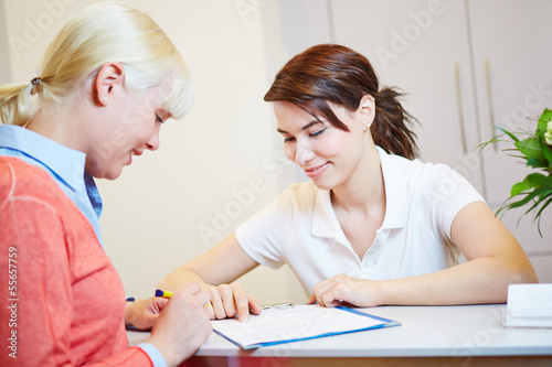 Patientin beim Arzt füllt Formular aus - 55657759