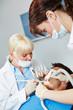 Zahnarzt bei Zahnbehandlung mit Zahnarzthelferin