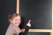Lustige Schülerin zeigt lachend auf Tafel