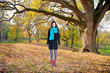 Beautiful girl in front of big tree in park