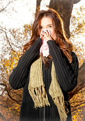 Caucasian woman with cold sneezing into tissue