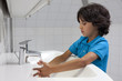 Little boy washing his hands