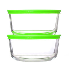 glass food containers with green plastic lids isolated