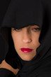 Woman in black cape with sad face