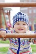 happy baby boy holding of climber on playground