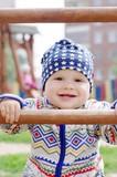 happy baby boy holding of climber on playground