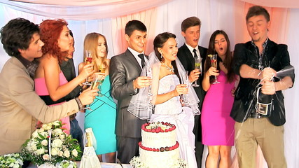 Group people open  bottle of champagne at wedding table.