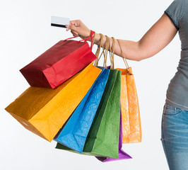Woman's hand holding shopping bags and credit card