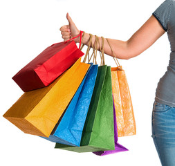 Female hand holding shopping bags and showing ok